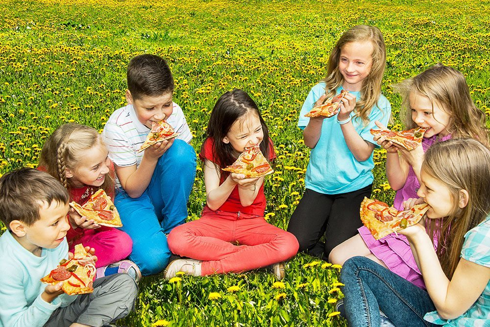 Group of children eating pizza outdoors